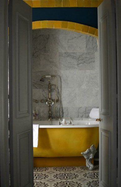 bathroom, black white patterned floor tiles, grey marble wall tiles, golden arch, yellow tub