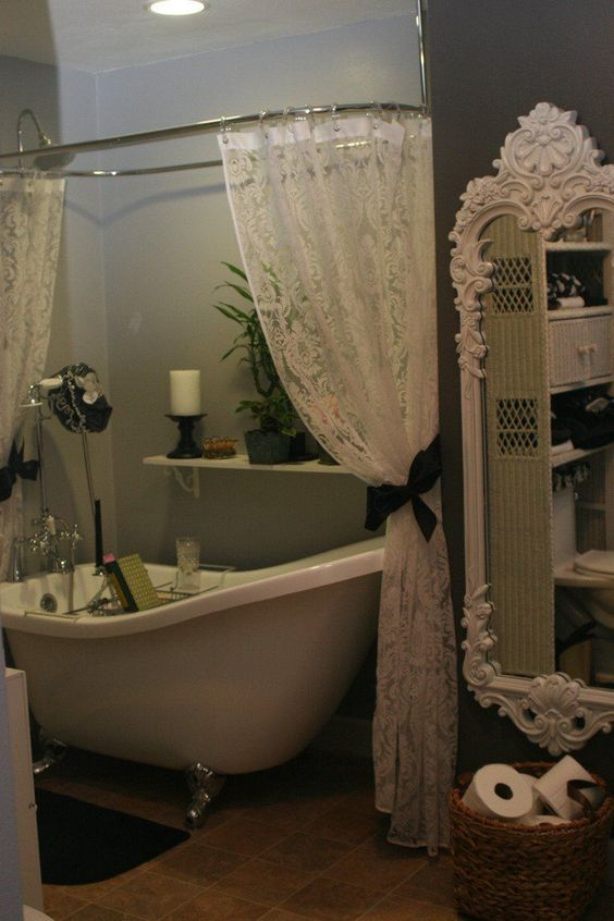 bathroom, brown floor tiles, grey wall, lace curtain, gey tub with white inside, white detailed mirror, rattan basket,floating shelves