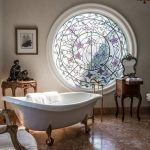 Bathroom, Brown Floor Tiles, White Tub, Claw Foot, White Wall, Round Glass Window With Patterned, White Chair, Brown Side Table, Chandelier