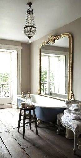 bathroom, wooden floor, blue tub, large golden mirror, crystal chandelier, white classic chair