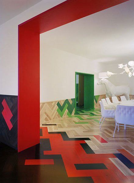 black red wooden green pink herringbone floor and wainscot pattern, white table, white chairs, white wall, red arch