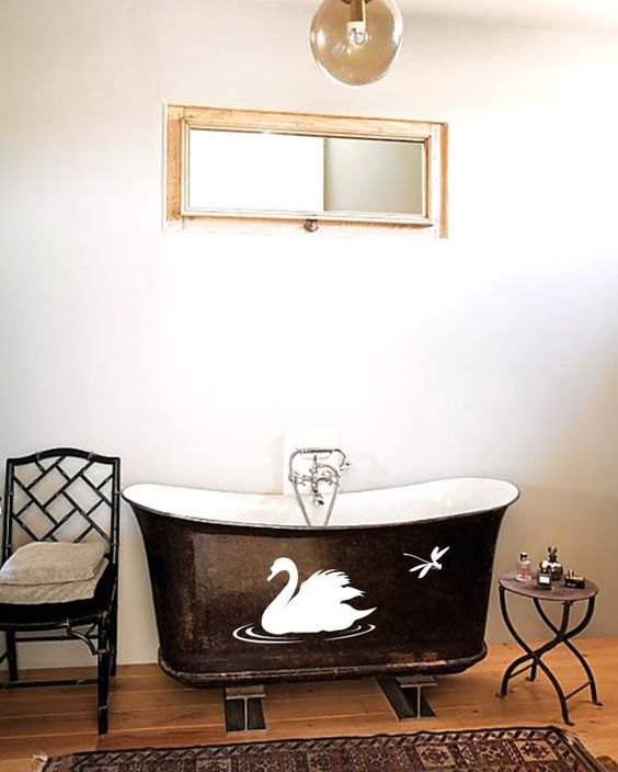 black tub with white swan on the body, wooden floor, black chair, white wall, mirror, clear glass pendant, side table
