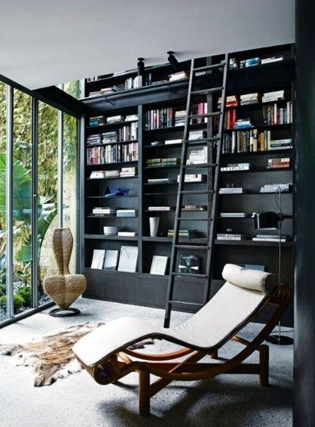 black wooden bok shelves with stairs, grey rug, lounge chair, near the sliding door