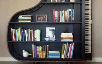 black wooden bookshelves in the shape of piano, wooden floor, green rug