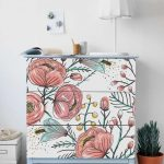 Blue Wooden Cabinet With Flowery Patterns In Front, Wooden Floor, White Wall, White Table Lamp