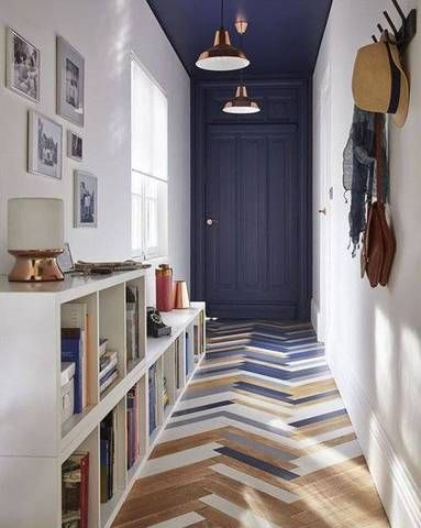 blue, wooden herringbone patterned tiles, dark blue ceiling, dark blue door, white wall, white bookshelves, pendant