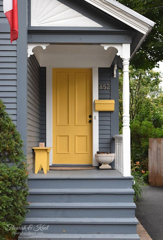 bold yellow door, yellor bench, grey wall plank, grey floor, grey stairs
