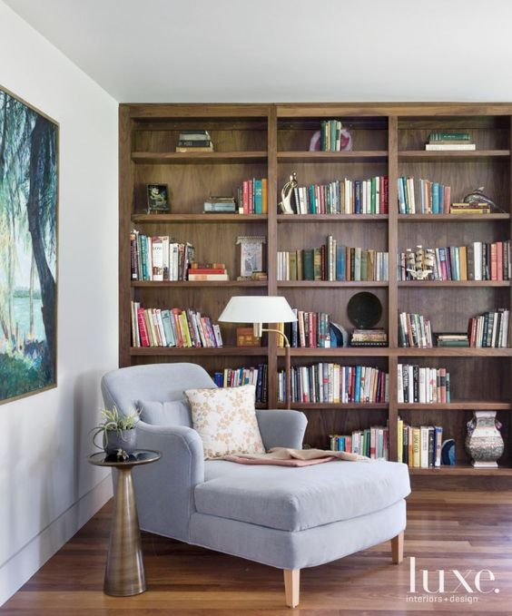 brown wooden shelves, white wall, blue lounge chair, round side table, wooden floor
