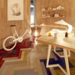 Colorful Herringbone Floor Tiles, Wooden Wall, Wooden Table, Wooden Shelves, White Bike