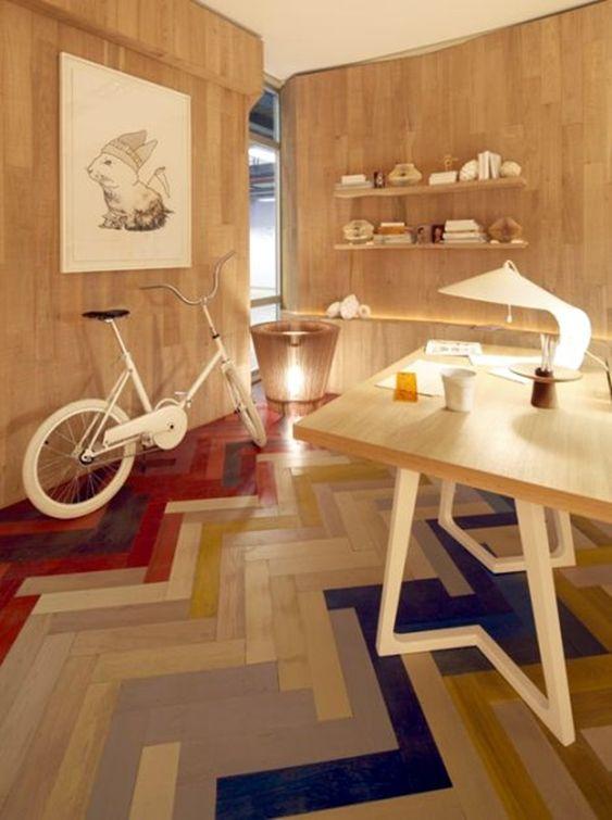 colorful herringbone floor tiles, wooden wall, wooden table, wooden shelves, white bike