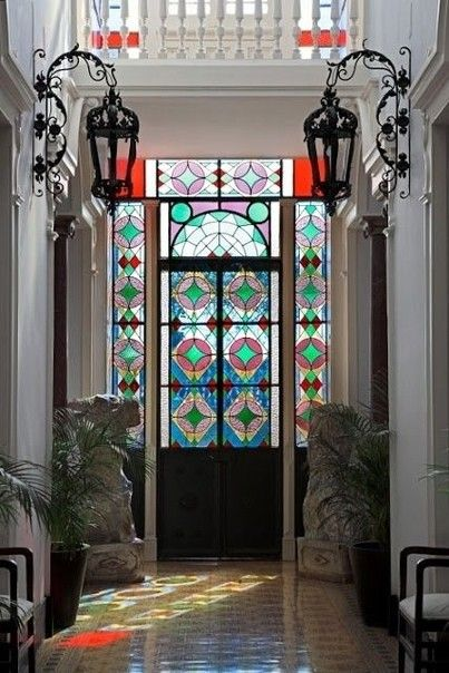 colorful stained glass on the window and door, white wall, black metal sconce, brown floor tiles