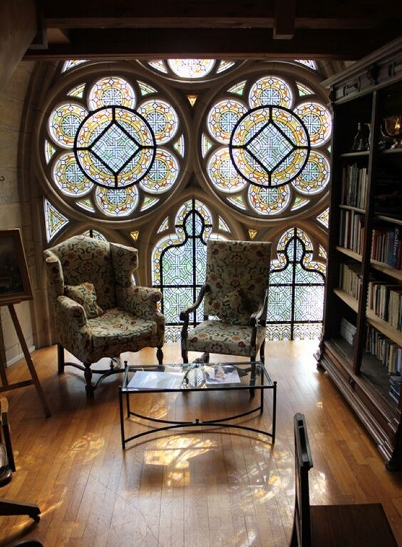 colorful stained glass on the window with flowery pattern, wooden floor, chairs with pattern, coffee table, bookshelves, wooden ceiling