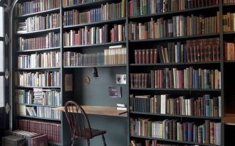 dark bookshelves, plaid floor, floating foldable table, white ceiling