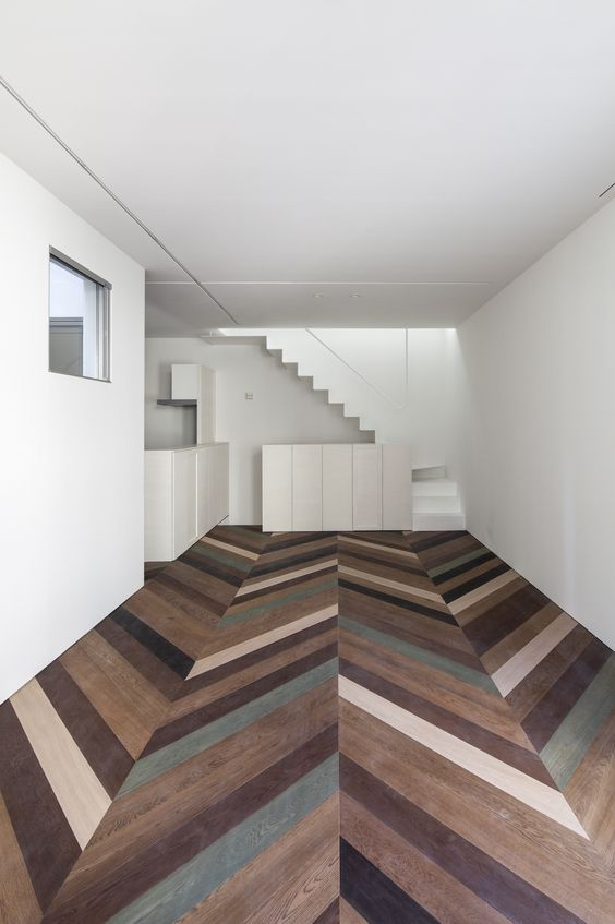 dark colored chevron pattern floor tiles, white wall, white ceiling