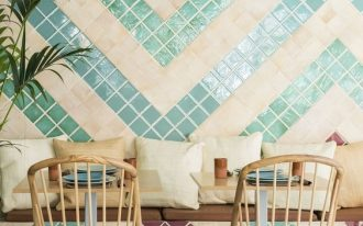 dining room, green white floor tiles, patterned tiles on the wall, wooden table, rooden chairs, floaring wooden bench, pillow, pendant