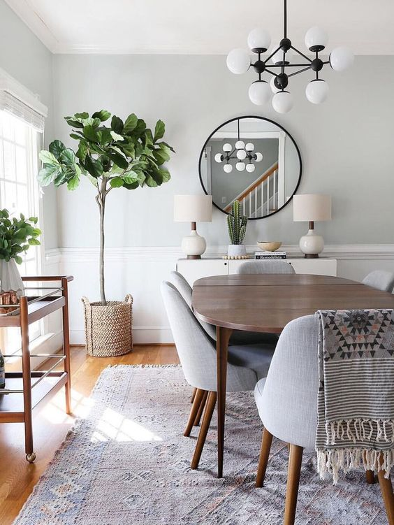 dining room, grey rug, wooden table, grey chairs, white chandelier, white wall, white wainscoting, rattan plant pot