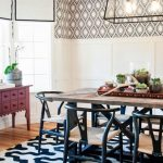 Dining Room, Wooden Floor, White Black Patterned Rug, White Wainscoting Wall, Patterned Wall, Rectangular Chandelier, Wooden Table, Black Metal Chairs With Rattan Seat