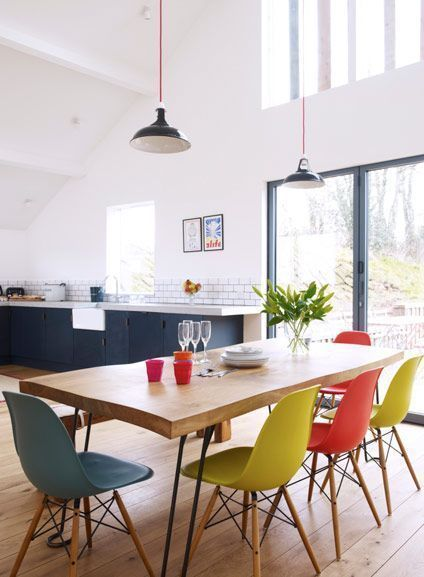 dining set, wooden table, colorful midcentury modern chairs, black pendants, white wall, kitchen with black bottom cabinet