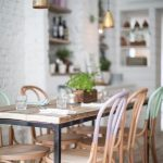 Dining Set, Wooden Table With Black Support, Pastel Colorful Wooden Chairs, Wooden Floor, White Open Brick Wall, Built In Shelves