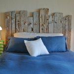 Diy Headboard Wooden Beach Headboard Blue Bedding Blue Pillows Wall Sconces Windows Shutters Hooks Rattan Side Table Indoor Plants