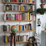Floating Book Shelves In The Living Room, Wooden Stool Wth Globe, Black White Chair, White Wall, Hanging Plants