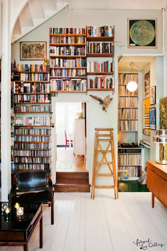 floating bookshelves in the living room follows the door lines, white wooden floor, black table, black leather chair, wooden cabinet