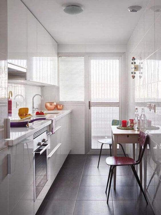 galley kitchen, grey floor tiles, white wall tiles, white cabinet, white top, table, stool