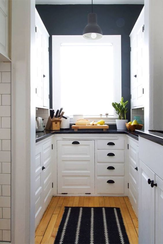 galley kitchen, wooden floor, black wall, black kitchen top, white cabinet, window, black pendant