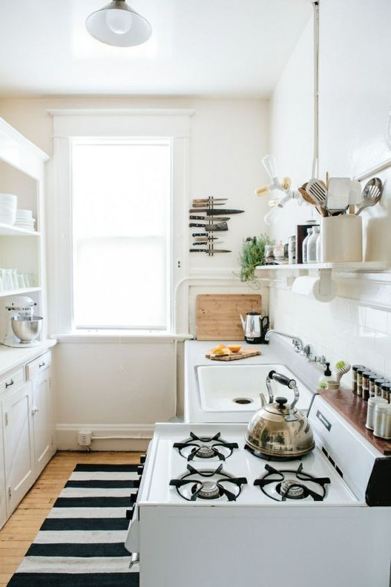 galley kitchen, wooden floor, white wall, white kitchen cabinet, white wink, white shelevs, white floating open shelves, white wtove, windows