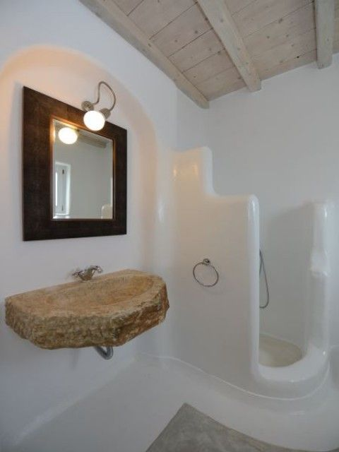 greek bathroom, white plaster wall and floor, floating stone sink, mirror, indented wall, wooden ceiling, grey rug