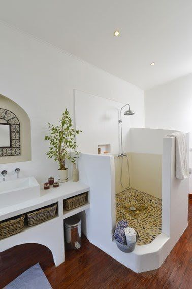 greek bathroom, wooden wall, tiles inside, half partition, white built in vanity, white sink, mirror