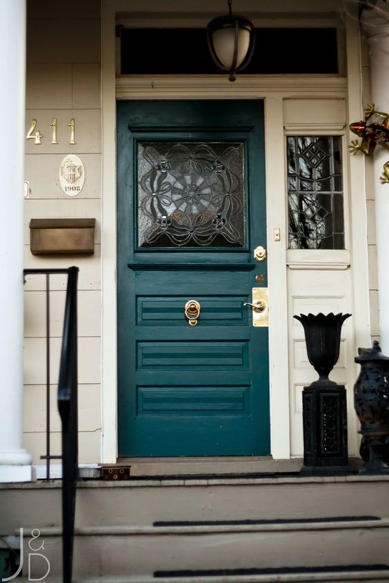 green painted door with patterned glass window, white plank wall, grey floor, stairs, pendant