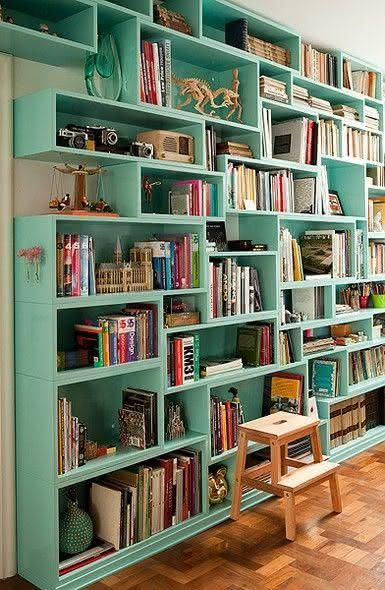 green wooden shelves, wooden floor, white wall, stool