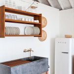 Grey Cube Sink On Wooden Table, Wooden Floating Shelves, White Wall, White Frige, Blue Chair, Grey Rug