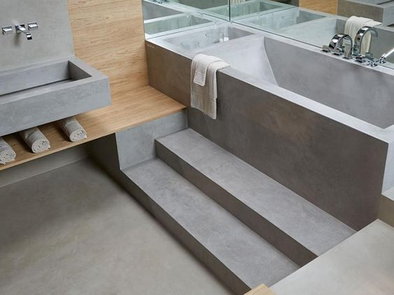 grey seamless bathroom, built in tub, vanity sink, wooden accent shelves