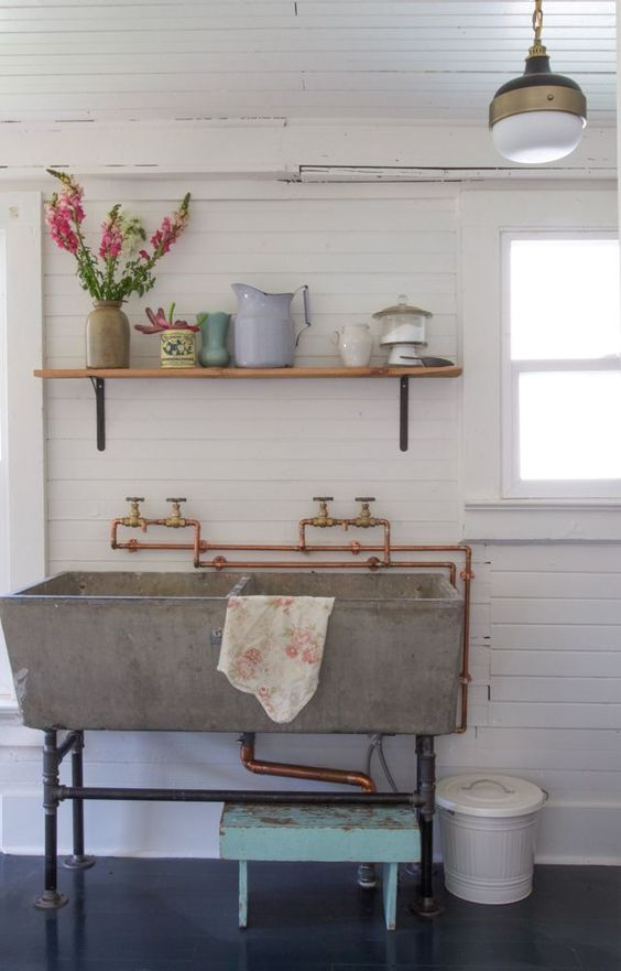 grey sink with double basin, white plank wall, white wooden ceiling, floating shelves, pendant, black floor