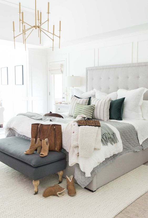 grey tufted headboard, grey bed platform, dark grey bench, white rug, beige floor, white wall, chandelier