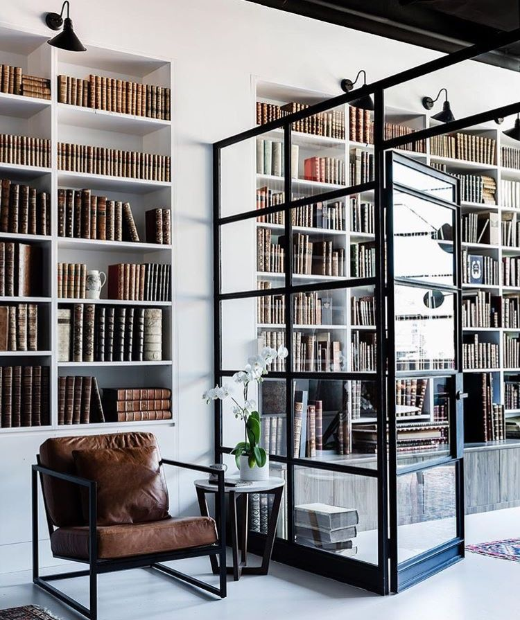hoome library, white built in shelves, white floor, glass partition, leather chair