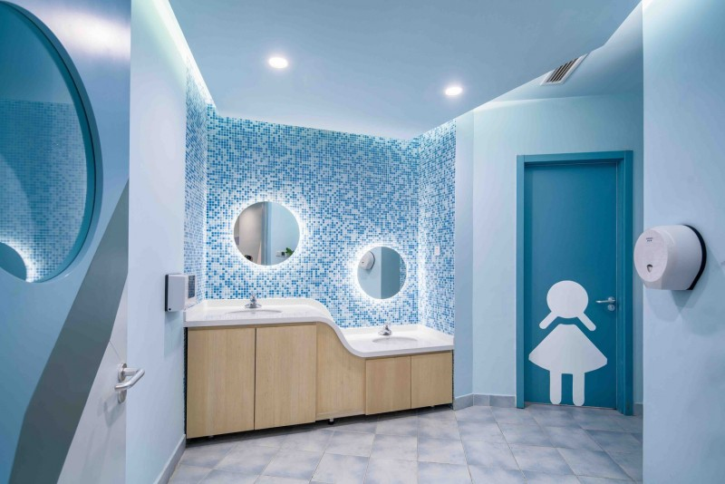 kids toilet, grey floor tiles, blue door, blue wall, blue mosaik backsplash, white top,wooden cabinet
