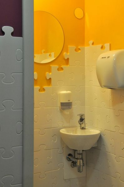 kids toilet, orange wall, white puzzle tiels, white round sink,