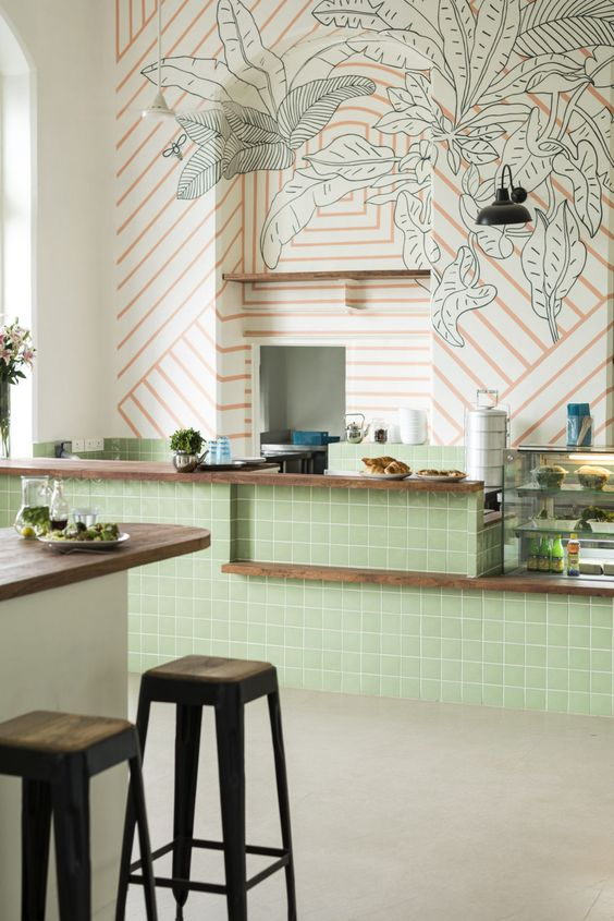 kitchen, beige floor, green tiles island, wooden kitchen top, orange striped with green leave wallpaper, island with wooden top, black stool