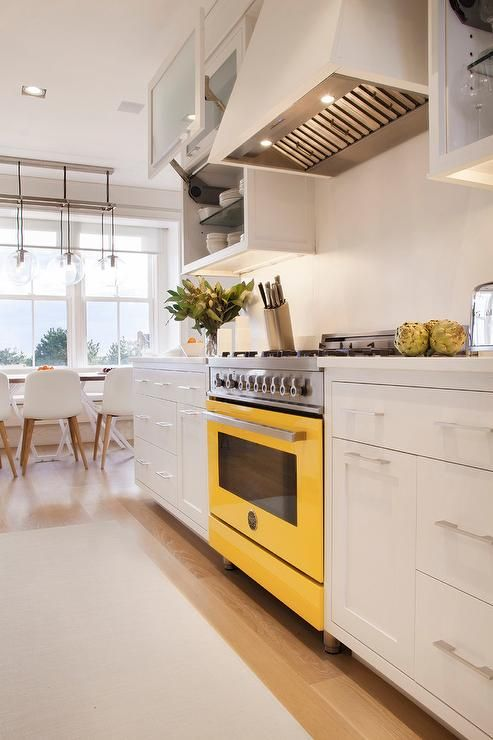 kitchen, wooden floor, white bottom cabinet, yellow stove, white backsplash, white upper cabinet, rug