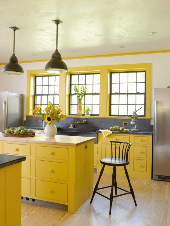 kitchen, wooden floor, wihte wall, yellow bottom cabinet, yellow island, grey kitchen top adn backsplash, apron sink, black pendant