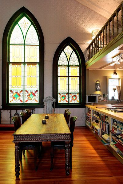 kitchen, wooden floor, yellow stained window with green arch frame, shelves with wooden top, white embossed wall, dining set