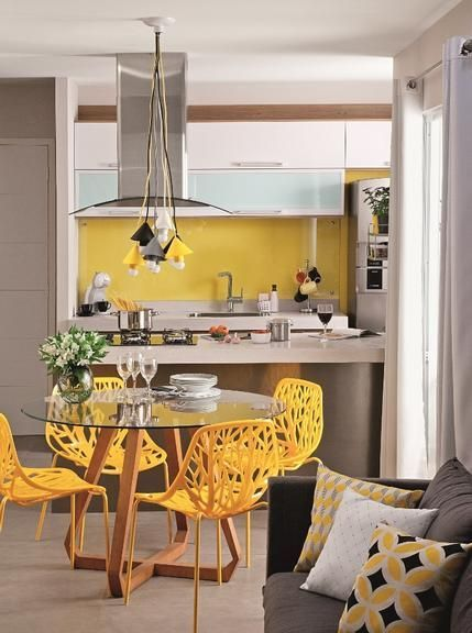 kitchen, yellow detailed chair, glass top round table, silver kitchen, yellow backsplash, yellow, white, black pendants, grey sofa
