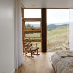 Large Glass Windows On The Bedroom With Some Small Rows Vertically On The Side, Wooden Floor, Wooden Rocking Chair, Wooden Platform With Bed Cushion