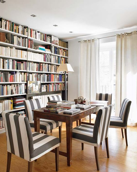 library, one side of the room for book shelves, wooden table, striped chairs, floor lamp