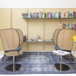 Library, Rattan Chairs, Golden Side Table, Floating Shelves, Yellow And White Wall, Blue Ruf, White Floor