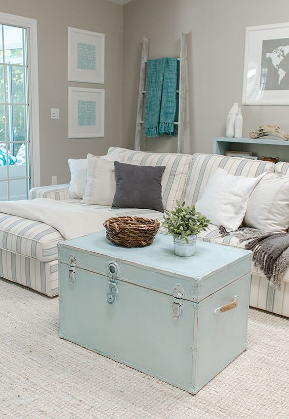 living room, beige rug, beige wall, striped sofa, blue chest coffee table, blue shelves