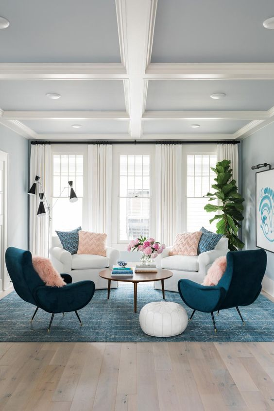 living room, blue rug, wooden floor, white wall, white ceiling, blue chairs, white chairs, wooden round coffee table